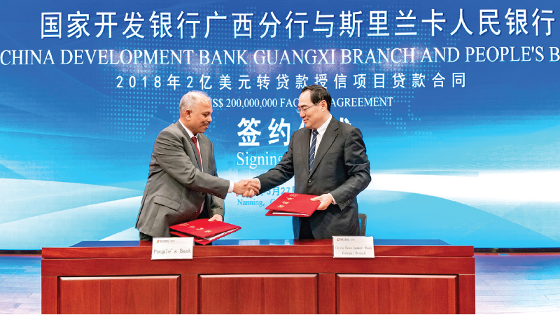 N. Vasantha Kumar (Chief Executive Officer/General Manager) of People's Bank and  Mei Shiwen (General Manager, Guangxi Branch) of China Development Bank signing the facility agreement
