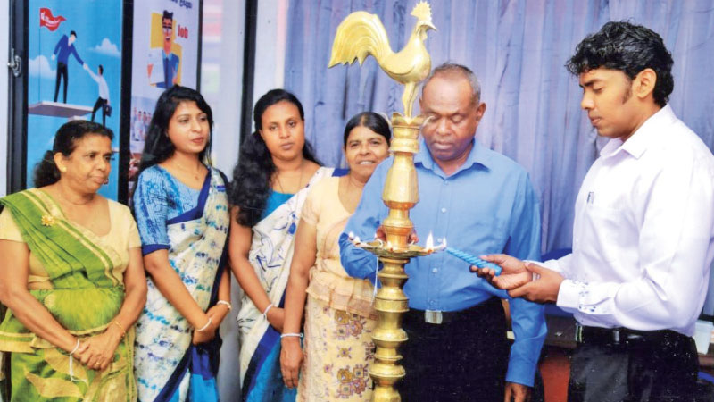 Senior Managers Sadun Priyankara Kasthuri  lighting the oil lamp accompanied by Managers Chamindi Weerasuriya and  Shani Serasinghe and other officials. Picture by Wimal Karunathilaka