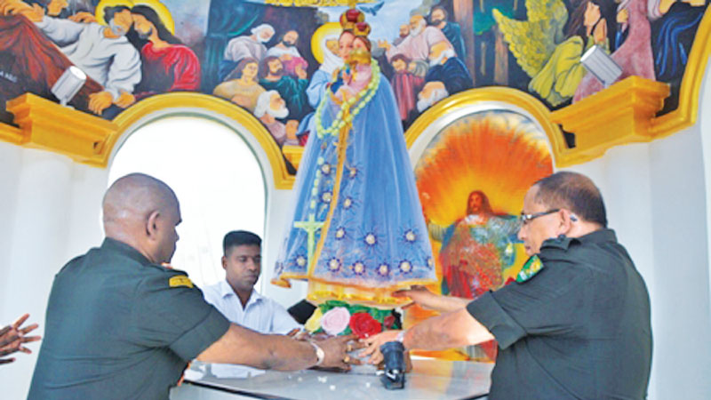 Army Commander Lieutenant General Mahesh Senanayake and Wanni Commander  Major General Kumudu Perera pay homage to the statue of Our Lady of Madhu at the Shrine, yesterday.