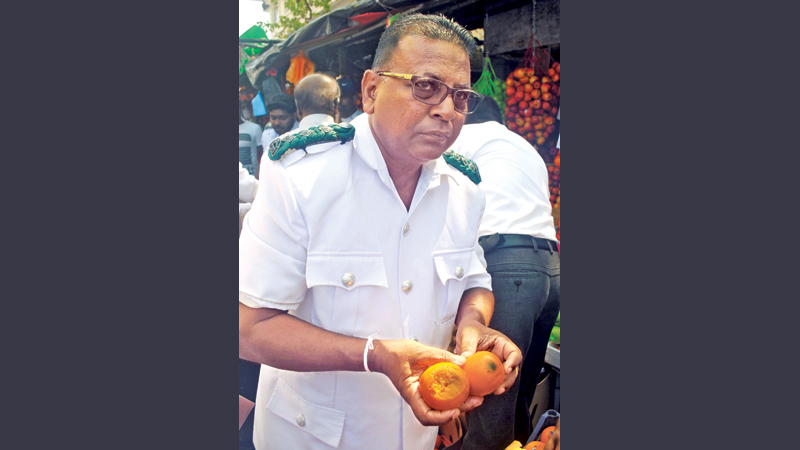 An officer shows rotten fruit found during a raid of the Pettah fruit market, recently. Picture by Siripala Halwala.