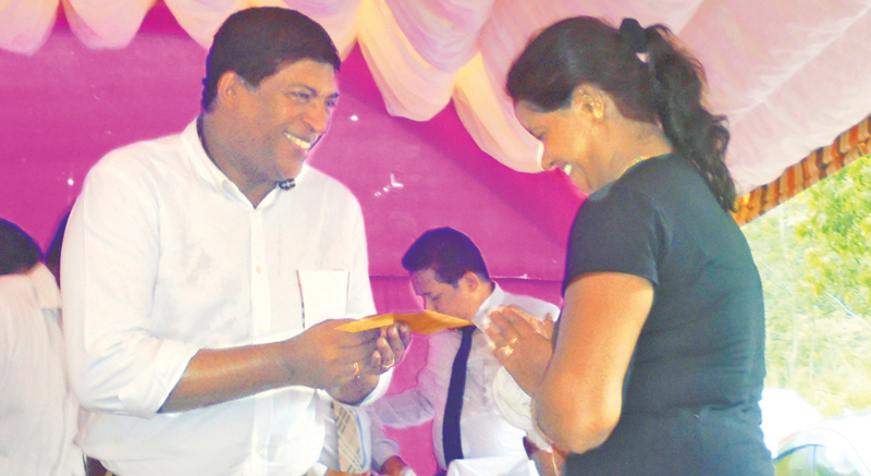 Minister Ravi Karunanayake offers compensation to an affected woman.