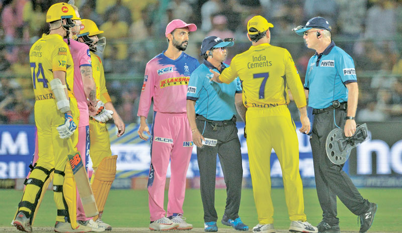 Chennai Super Kings cricketer and team captain MS Dhoni (C) argues with match umpires during the 2019 Indian Premier League (IPL) Twenty20 cricket match against Rajasthan Royals at Jaipur on Thursday. - AFP