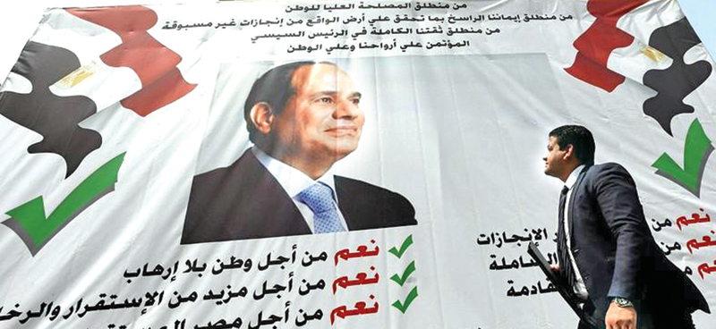 A man walks in front of a banner with a photo of the Egyptian President Abdel-Fattah al-Sisi before the approaching referendum on constitutional amendments  in Cairo.