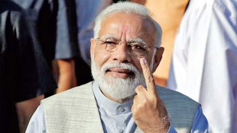 Indian Prime Minister Narendra Modi shows his ink-marked finger after casting his vote outside a polling station during the third phase of general election in Ahmedabad yesterday.