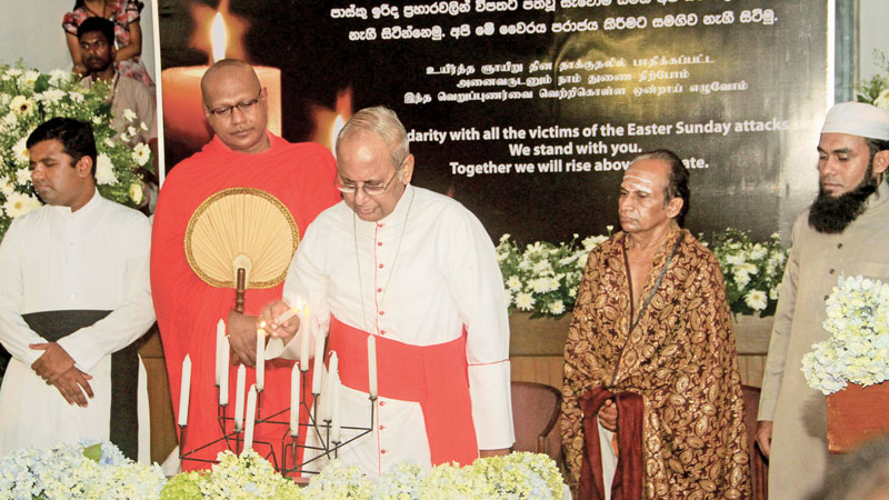 A solemn but dignified ceremony was held at the Lake House premises last evening to commemorate those who died during the Easter Sunday carnage inflicted by terrorists. Archbishop of Colombo His Eminence Malcolm Cardinal Ranjith, Most Ven. Dr. Kirinde Assaji Thera of the Gangaramaya temple, Shri Shankara Narayana Kurukkal of Shri Mayurapathy Kovil and Nusrath Nawfel Moulavi joined together to light a candle in memory of the departed souls. Picture by Sudam Gunasinghe