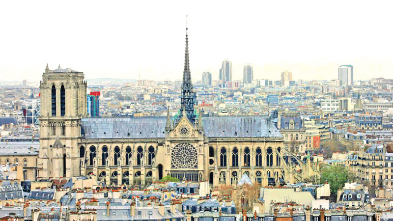 A city view shows the Notre Dame Cathedral in this March 30, 2016 file photo as part of the skyline in Paris, France. The April 15, 2019 fire toppled the Gothic landmark's spire and damaged the roof.