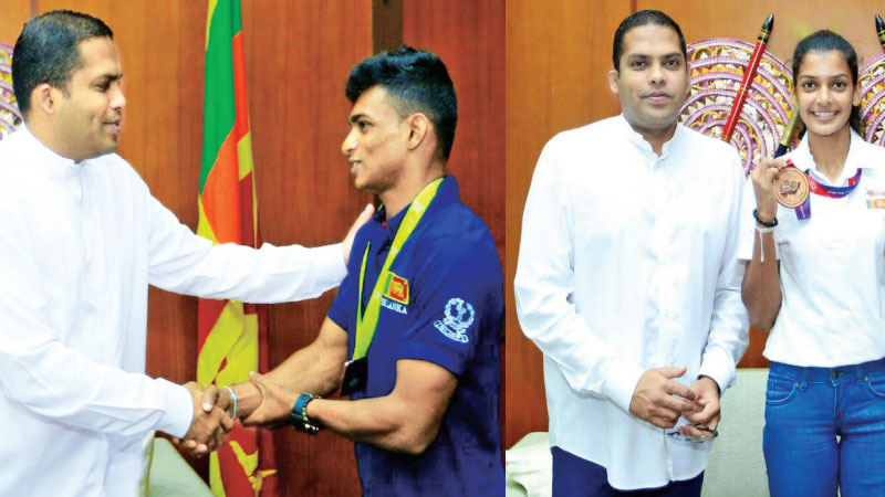 Sports Minister Harin Fernando congratulates weightlifting bronze medalist Lance Corporal YDI Kumara (on left) and Vidusha Lakshani who won a bronze medal in athletics.