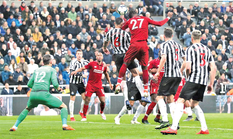 Liverpool's Divock Origi scores their third goal in their Premier league match against Newcastle.