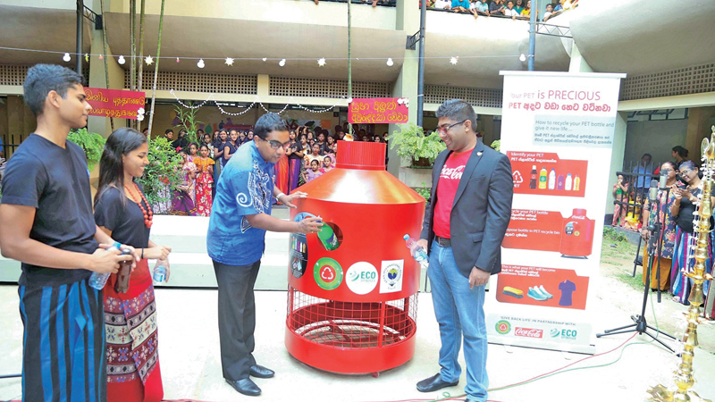 Harshana Perera putting the first plastic bottle into the PET bins while Lakshan Madurasinghe Country Public Affairs, Communications and Sustainability Manager and Head Prefects, Shahane De Silva and Hemali Ratnaweera look on.