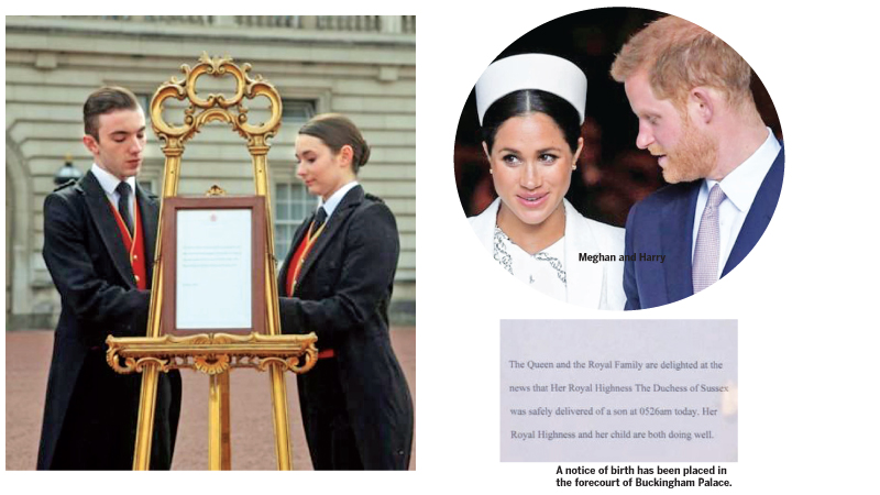 Footmen Stephen Kelly and Sarah Thompson set up an official notice on an easel at the gates of Buckingham Palace in London on May 6, 2019, announcing the birth of a son to Prince Harry, Duke of Sussex and Meghan, Duchess of Sussex. - AFP