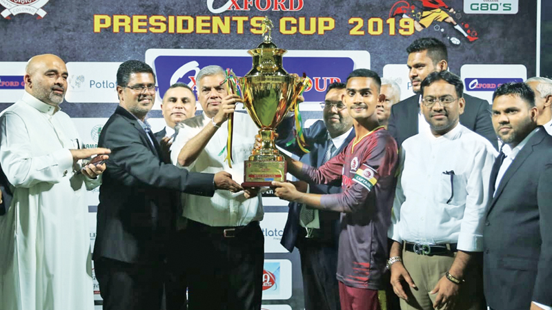 Captain of the champion Hameed Al Husseinie College M.S.M. Safrin receiving the trophy from the chief guest, Prime Minster Ranil Wickremesinghe.