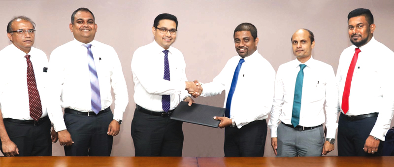 Commercial Bank's Chief Operating Officer Sanath Manatunge and Browns Agriculture General Manager Sanjaya Nissanka exchange the agreement in the presence of Commercial Bank's Manager Retail Lending Department Chandana Abeysundara, the Bank's Deputy General Manager Marketing Hasrath Munasinghe, Browns Agriculture Deputy General Manager Niyas Ahamed and Business Development Manager Chanaka Chandrasekara.