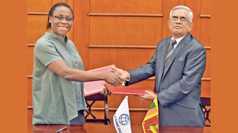 Finance Ministry Secretary Dr. R.H.S. Samaratunga and World Bank Country Director for Sri Lanka and Maldives Ms. Idah Z Pswarayi – Riddihough exchanging  the Loan Agreement at the Ministry of Finance yesterday.