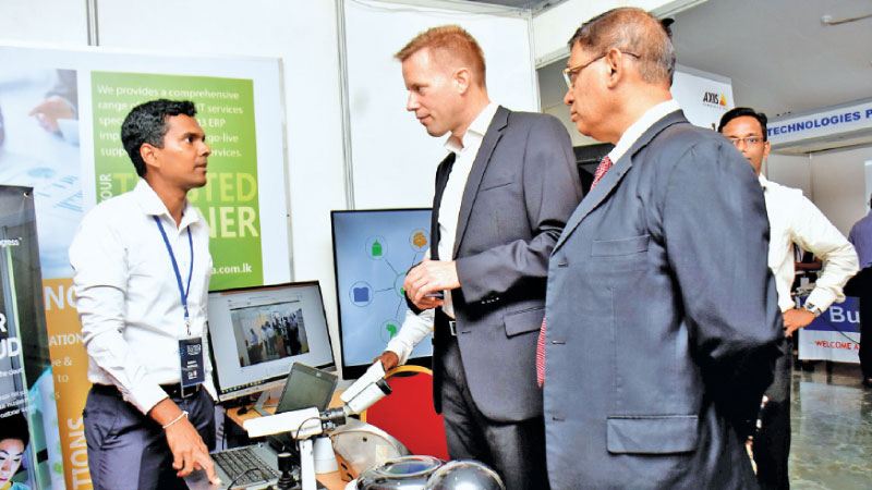 Group Chief Operating Officer, Dialog Axiata, Dr.Rainer Deutschmann and President, CA Sri Lanka, Jagath Perera visit a stall at the fair. Picture by: Gayan Pushpika