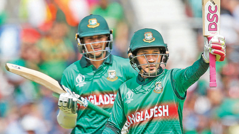 Bangladesh's Mushfiqur Rahim (R) acknowledges the crowd as he celebrates after scoring a half-century (50 runs) as teammate Shakib Al Hasan looks on during the 2019 Cricket World Cup group stage match between South Africa and Bangladesh at The Oval in London on June 2. AFP