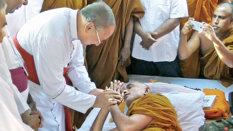 Colombo Archbishop Malcolm Cardinal Ranjith speaks to Ven. Rathana Thera who was on the fourth day of his hunger strike. Picture by Asela Kuruluwansa