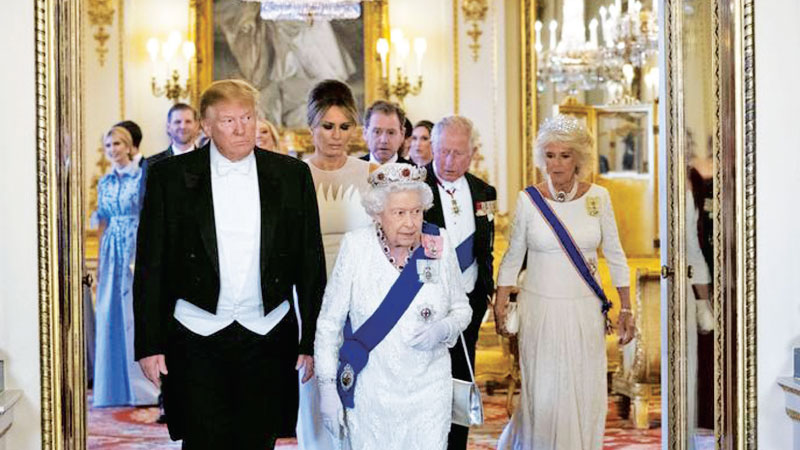 US President Donald Trump walks with Queen Elizabeth II, followed by First Lady Melania Trump, Prince Charles, and Camilla, Duchess of Cornwall, as they make their way into the Music Room for a State Banquet at Buckingham Palace on Monday.