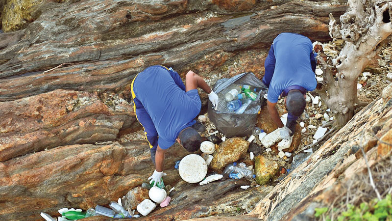 Naval personnel clean the beach adjacent to the Dutch Fort in Galle to coincide with World Environment Day.