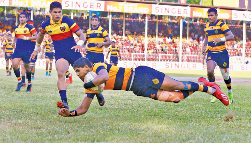Royal College centre Lehan Gunaratne flies over the line to score a try against Trinity College.