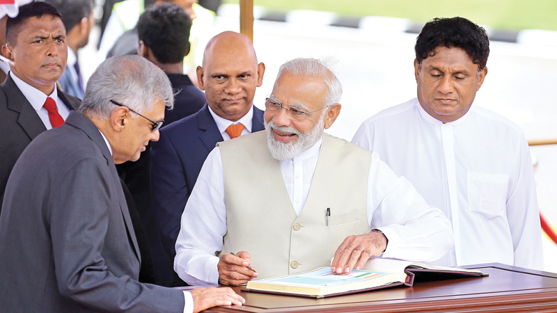 Indian Prime Minister Narendra Modi signing the Special Visitors' Book in the presence of Prime Minister Ranil Wickremesinghe and Minister Sajith Premadasa, upon his arrival at the Bandaranaike International Airport, yesterday.