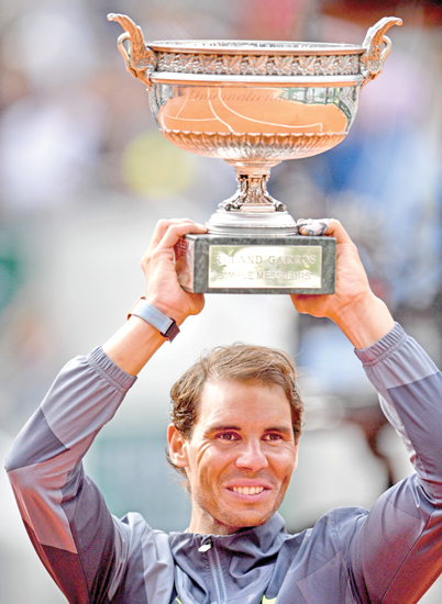 Spain's Rafael Nadal poses with the Mousquetaires Cup (The Musketeers) at the end of the men's singles final match against Austria's Dominic Thiem on day fifteen of The Roland Garros 2019 French Open tennis tournament in Paris