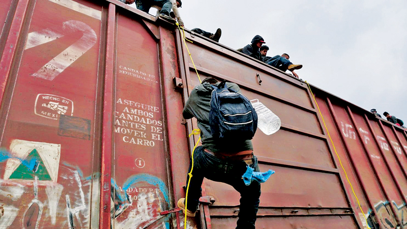 """Central American migrants climb on the train known as """"the beast"""" in Ixtepec, Mexico, on their way to the United States."""