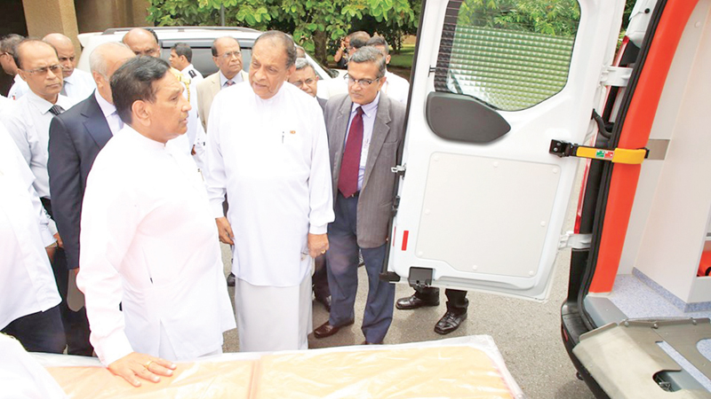 Health Minister Dr. Rajitha Senaratne with Speaker Karu Jayasuriya at the handingover of the ambulance. Officials of the Health Ministry and Parliament look on.