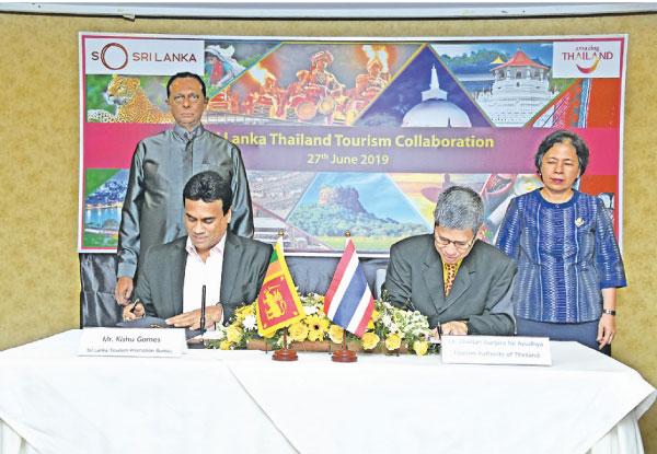 Chairman, Sri Lanka Tourism Promotion Bureau Kishu Gomes and Governor of the Tourism Authority of Thailand, Yuthasak Supasorn sign the MoU at Colombo Hilton. Picture by Saliya Rupasinghe