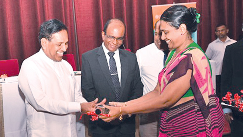 Health Minister Dr. Rajitha Senaratne presents an award during the ceremony.