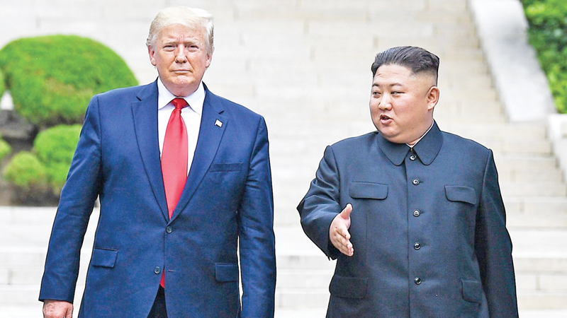 North Korean leader Kim Jong Un walks with US President Donald Trump north of the Military Demarcation Line in Panmunjom in the Demilitarized zone (DMZ). - AFP