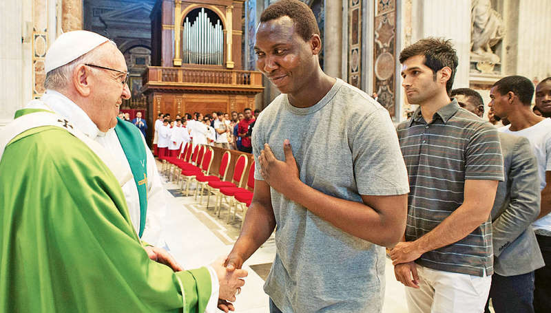 Pope Francis is greeted by a migrant at a mass to commemorate the fifth anniversary of his visit in Lampedusa. – The Guardian