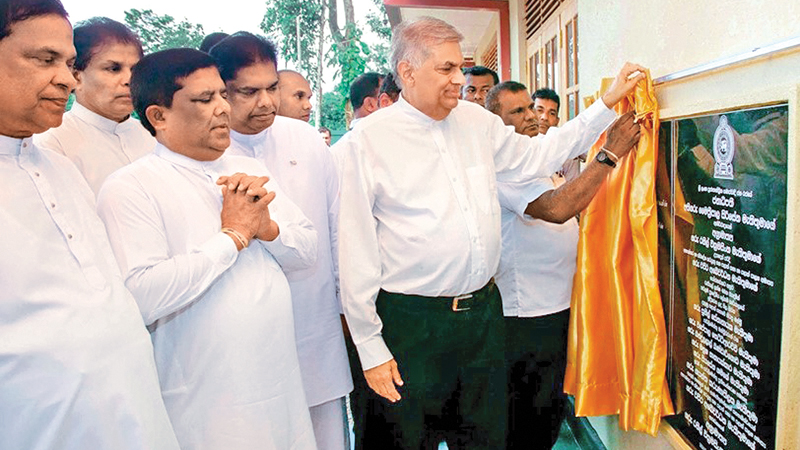 Prime Minister Ranil Wickremesinghe unveils the plaque to mark the inauguration of the new building complex at the Thawalama Vidyaraja National School.