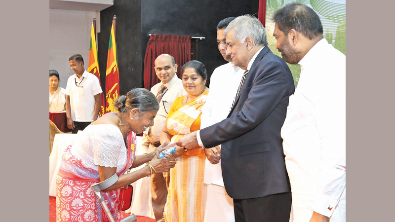 Prime Minister Ranil Wickremesinghe presenting financial assistance to a winner of the Samurdhi Housing Lottery Draw for the month of May at a ceremony held at Temple Trees yesterday. Picture courtesy Prime Minister's Media Division