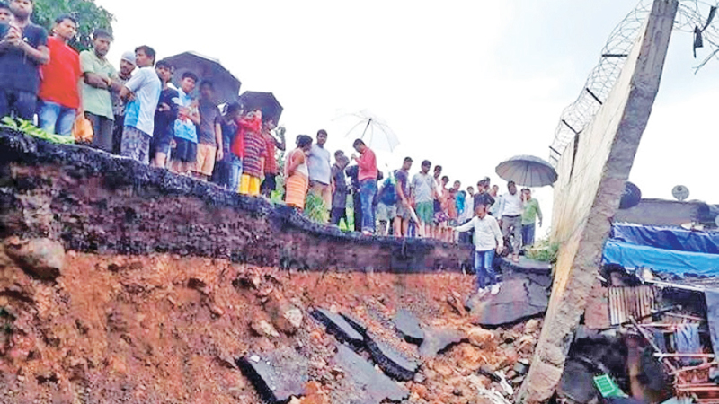 Rescuers and onlookers stand at the spot of a wall collapse in Mumbai, India yesterday.
