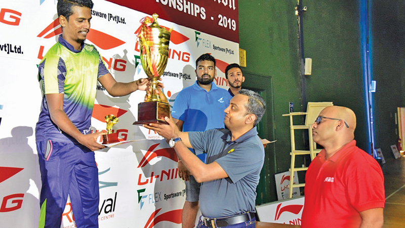 Thushan Gomes  from Expo Lanka receiving men's novices champion award from chief guest Sanjeewa Akuretiya MD of Flex Sports Wear Pvt Ltd at the awards ceremony of the Mercantile Novices Badminton championships . Mercantile Badminton Association President and Vice President of SLB Roshan Fernando is also present