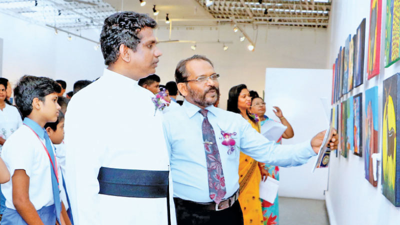 Fr. Gemunu Dias views the exhibits at the Lionel Wendt on Tuesday. Picture by Gayan Pushpika