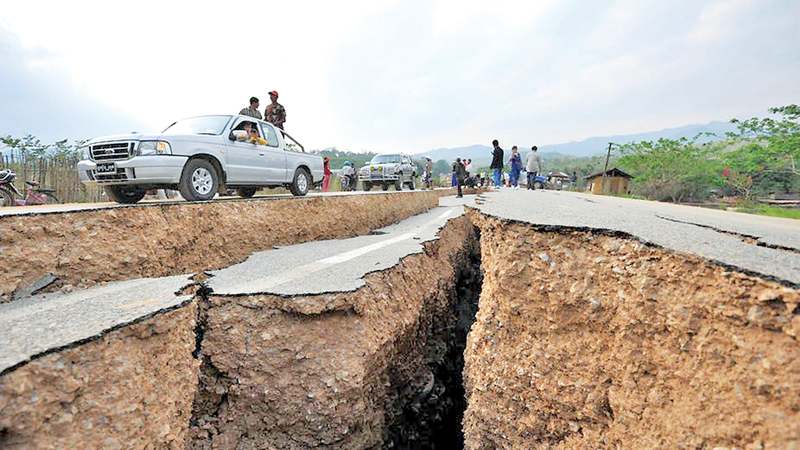Cars drive past cracks on the road after last Friday's earthquake.