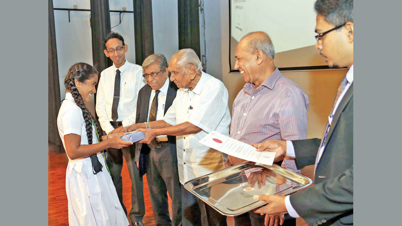 Kalakeerthi Dr. Edwin Ariyadasa presents a prize to one of the winners of the essay competition, at the Centre for Banking Studies yesterday. Picture by Sulochana Gamage