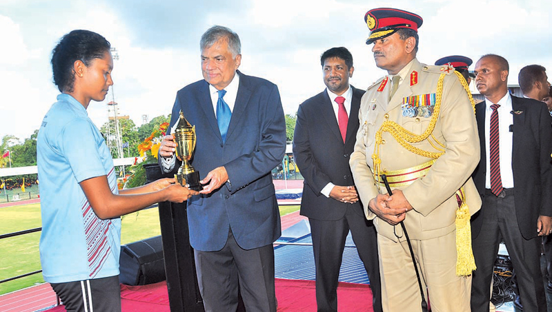 A cadet receiving the trophy from Prime Minister Ranil Wickremesinghe while State Minister of Defence Ruwan Wijewardene looks on.