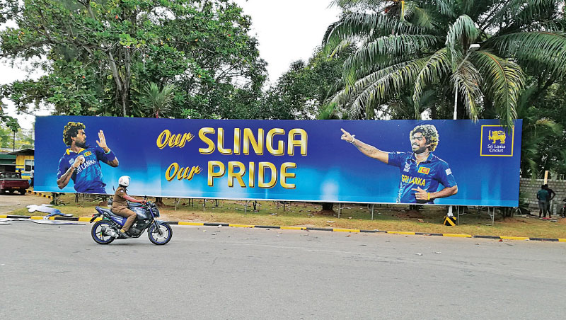 A traffic policeman rides past a banner at the R Premadasa Stadium saluting cricket legend Lasith Malinga on his final ODI appearance for his country in the first match of a three-match series against Bangladesh today. (Picture by Ishara Kodikara)