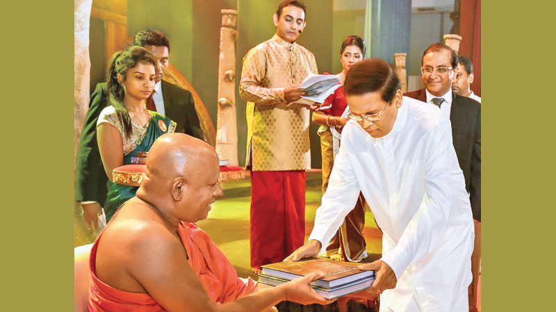 "President Maithripala Sirisena presenting the research-based scholarly volume ""Polonnaruwa – Narapathi Yugaye Sita Janapathi Yugaya Dakwa"" to the Maha Sangha at the launch ceremony held at BMICH yesterday evening. Picture courtesy President's Media Division"