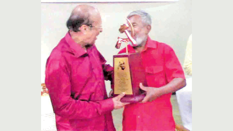 Communist Party Galle District Secretary G. Deneththi presents a memento to DEW Gunasekara, at the event. Picture by Mahinda P. Liyanage, Galle Central Special Corr.