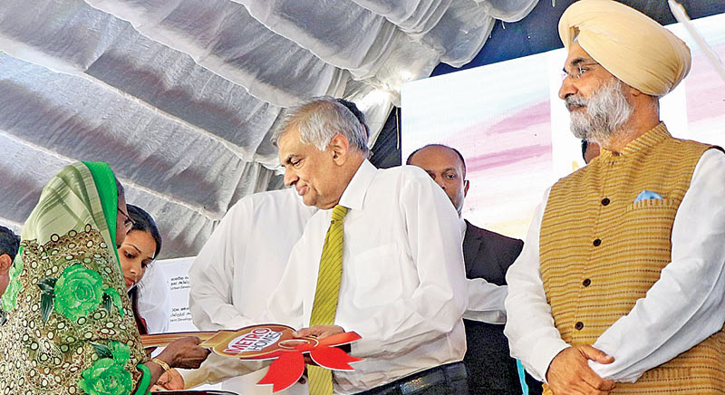 Prime Minister Ranil Wickremesinghe handing over the key to one of the beneficiaries of the housing scheme. Minister Champika Ranawaka and India's High Commissioner to Sri Lanka Taranjit Singh Sandhu look on. Pictures by Hirantha Gunathilake.