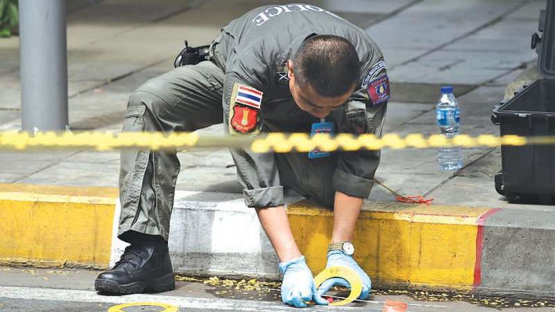 A policeman collects evidence at the scene of yesterday's explosion in Bangkok.