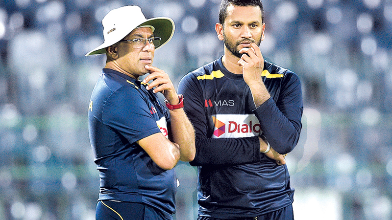 Test skipper Dimuth Karunaratne (right) will have Chandika Hathurusingha as head coach for the two-Test series against New Zealand if the Sports Minister okays Sri Lanka Cricket's request.