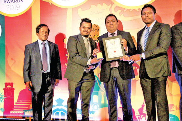 Indika Jayapala, CEO - Ribelz Integrated receives the award from Minister of Education Akila Viraj Kariyawasam. Ushan Wijewardena, Head of Marketing and New Business, TVS Lanka, while Prof. Gunapala Nanayakkara looks on.