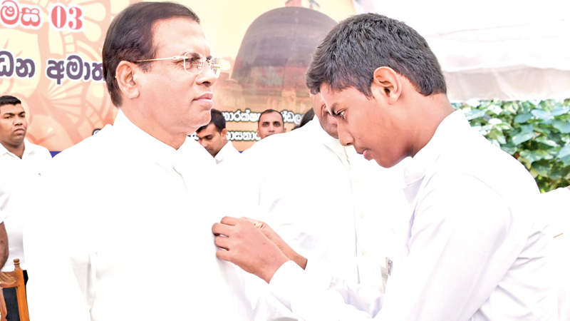 A student pins the Sunday School Flag on President Maithripala Sirisena, at the event. Picture courtesy President's Media Division