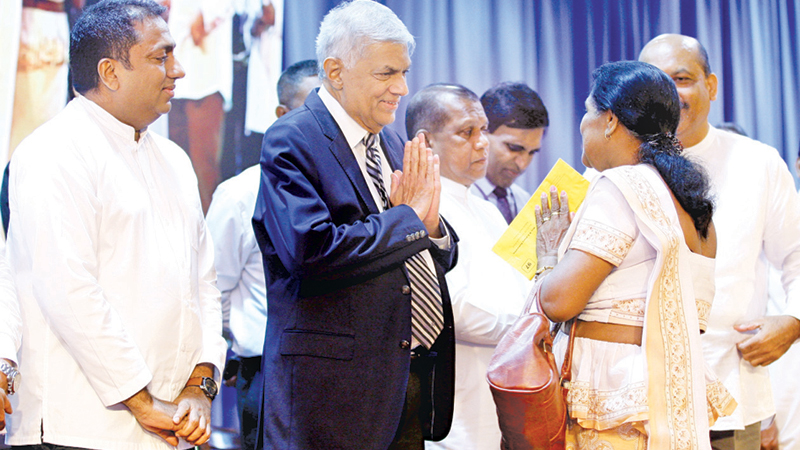 Prime Minister Ranil Wickremesinghe greets a recipient of compensation, at Temple Trees yesterday. Picture by Hirantha Gunathilaka