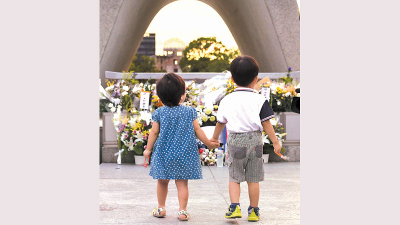 Two children stand in front of the cenotaph at the Hiroshima Peace Memorial Park on Tuesday.