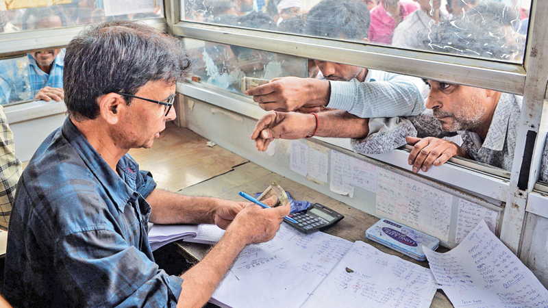 Labourers buy bus tickets at a counter of Jammu and Kashmir Tourist Reception Centre (JKTRC) in Srinagar. - AFP
